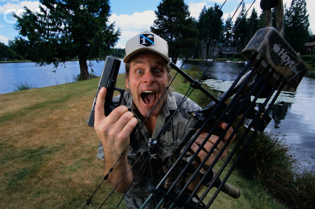 Ted Nugent Holding Pistol and Bow